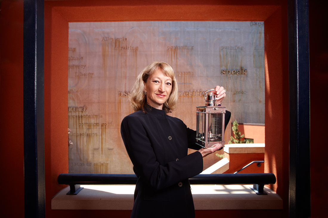 Environmental Portrait of a female executive standing in front of an interesting wall and holding a lantern.