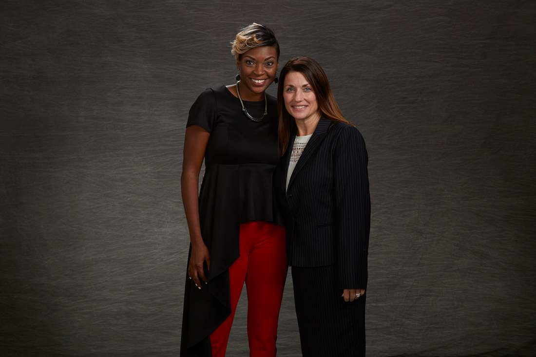 Speaker Jade Simmons standing with Sacramento Metro employee Susan Harris smiling and posing infant of grey background at the Perspectives of leadership event at the Sacramento Civic Center
