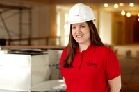 Professional on-site business portrait of girl with hard-hat facing camera.