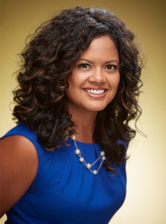 Business headshot of a female professional in a blue top smiling at the camera in front of a gold background.