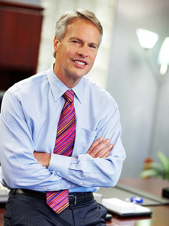 Professional business headshot of an executive casually posing in his office while smiling at the camera.