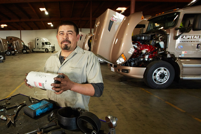 Commercial photography of an auto repairman standing in front of a fleet of Capital Express Line Big Rigs