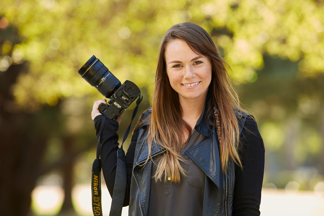 Kristin Van-Y standing holding Nikon camera in front of a blurred nature scene wearing a leather jacket and smiling.