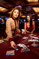 Portrait of a blackjack dealer in a Casino at a blackjack table dealing cards with a woman playing cards smiling at the camera.