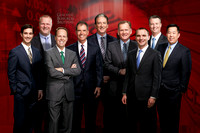 9 executives in suits stand smiling as group in front of a red Genovese Burford and Brothers's branded background