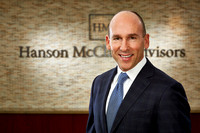 Business headshot of male executive at Hanson McClain Advisors casually smiling at the camera in a nice suit.